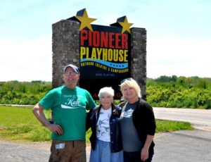 The Hensons--Robby, Charlotte, Heather--stand proudly in front of the new sign